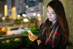 使用智能手机的妇女在城市 免版税库存图片
