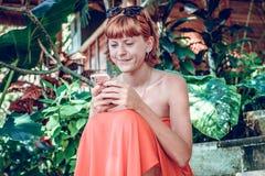 使用智能手机的妇女在热带庭院 假期 热带海岛努沙Lembongan,巴厘岛,印度尼西亚 免版税库存照片