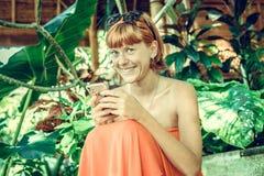 使用智能手机的妇女在热带庭院 假期 热带海岛努沙Lembongan,巴厘岛,印度尼西亚 免版税库存图片