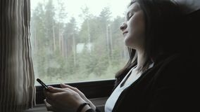 使用智能手机的妇女在窗口旁边在移动的火车,旅行概念 影视素材