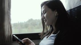 使用智能手机的妇女在窗口旁边在移动的火车,旅行概念 股票视频