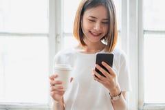 使用智能手机的妇女,在悠闲时间 r 免版税库存照片