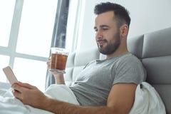 使用智能手机的学士人每日定期唯一生活方式早晨概念饮用的茶 免版税库存照片