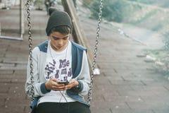 使用智能手机的孩子在摇摆 库存图片