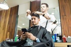 使用智能手机的客户,当给他理发时的美发师 免版税库存图片