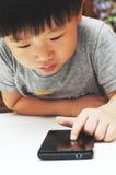 使用智能手机的小男孩 免版税库存照片