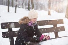 使用智能手机的少女在冬天季节的公园 库存照片