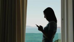 使用智能手机的少妇剪影  在窗口的白种人式样身分和使用她的智能手机 影视素材