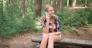 使用智能手机的少妇在森林 库存图片