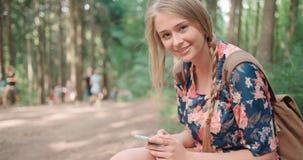 使用智能手机的少妇在森林 免版税库存照片