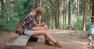 使用智能手机的少妇在森林 免版税库存图片