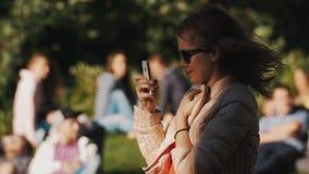 使用智能手机的少妇外面在公园在夏天事件期间 许多人 股票视频
