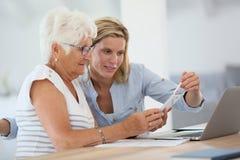 使用智能手机的少妇帮助的老人 库存照片