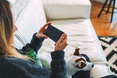 使用智能手机的少妇 附近有狗 女孩工作,在网上学会,检查电子邮件 距离工作 免版税图库摄影