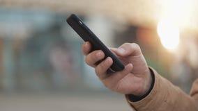 使用智能手机的年轻人的手在街道在购物中心附近 通信,网络购物,闲谈,社会 股票视频