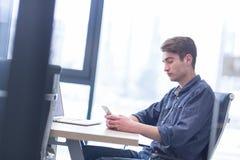 使用智能手机的年轻偶然商人 免版税库存图片