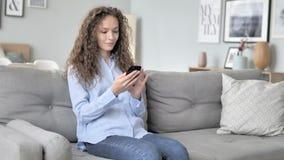 使用智能手机的年轻卷发妇女,当放松在沙发时