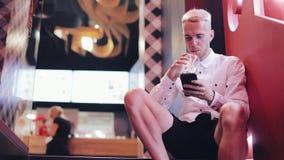 使用智能手机的年轻可爱的人晚上 坐在夜总会neara霓虹标志和饮用的鸡尾酒的他 股票视频