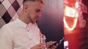 使用智能手机的年轻可爱的人晚上 站立在酒吧或餐馆的他在霓虹标志和喝附近 影视素材