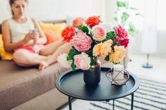 使用智能手机的年轻女人在家坐长沙发 用玫瑰花束装饰的客厅  免版税库存照片