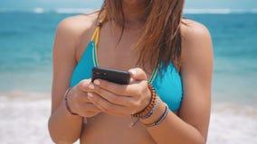 使用智能手机的年轻女人在海滩在海洋背景 微笑的女性游人是泳装在假期时在巴厘岛 股票录像