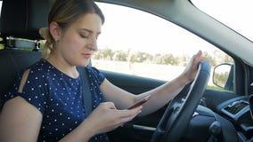 使用智能手机的年轻女人慢动作英尺长度,当驾驶汽车时 请用途没有雇工在您的安全的车 股票视频