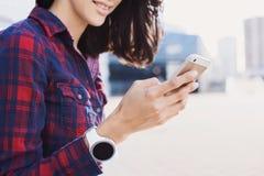 使用智能手机的年轻女人户外 免版税库存照片