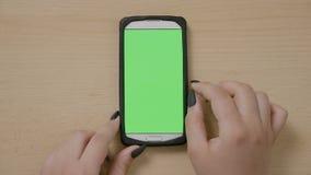 使用智能手机的年轻女实业家顶视图做卷动和滑姿态在绿色触摸屏幕- 影视素材