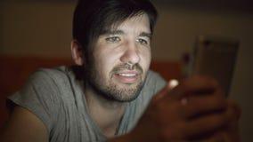 使用智能手机的年轻微笑的人特写镜头为冲浪在家说谎在床在晚上的社会媒介 影视素材