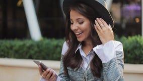使用智能手机的年轻愉快的妇女站立整洁的办公室中心 概念:新的事务,通信,银行家 外面 股票视频