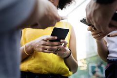 使用智能手机的年轻成人朋友户外 免版税库存照片