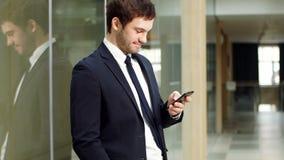 使用智能手机的年轻成功的商人画象和看照相机在现代办公室 影视素材