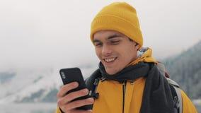 使用智能手机的年轻旅客人在远足冬天游览 斯诺伊弄脏了山海角和湖 旅行和 影视素材