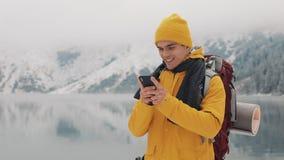 使用智能手机的年轻旅客人在远足冬天游览 斯诺伊弄脏了山海角和湖 旅行和 股票录像