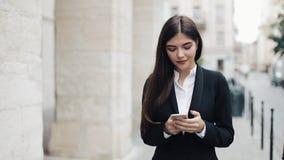 使用智能手机的年轻美丽的女商人 浏览互联网的她 非常愉快女孩的微笑和的神色 概念 股票视频