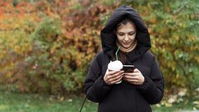 使用智能手机的年轻美女在秋天公园 免版税库存图片