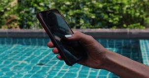 使用智能手机的庄稼手在游泳场附近 股票视频