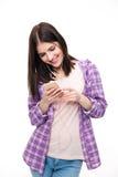 使用智能手机的微笑的妇女 免版税库存图片