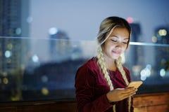 使用智能手机的微笑的少妇在晚上都市风景 库存图片