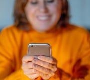 使用智能手机的微笑的年轻女人在流动瘾和网上约会 库存照片