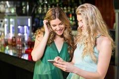 使用智能手机的微笑的朋友 免版税库存图片