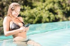 使用智能手机的微笑的金发碧眼的女人在水池 免版税库存照片