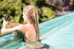 使用智能手机的微笑的金发碧眼的女人在水池 库存图片