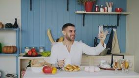 使用智能手机的快乐的年轻人为与女朋友的网上录影闲谈,当吃早餐早晨时 库存图片