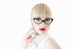 使用智能手机的性感的白肤金发的商业主管。 免版税库存照片