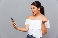 使用智能手机的恼怒的偶然妇女隔绝在灰色背景 图库摄影