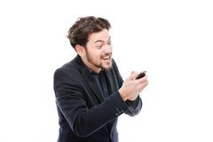 使用智能手机的恼怒的商人 免版税库存照片