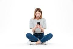 使用智能手机的惊奇的妇女 库存图片