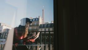 使用智能手机的愉快的典雅的女实业家在田园诗晴朗的早晨巴黎阳台,令人惊讶的看法通过玻璃窗 股票录像