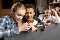 使用智能手机的愉快的多文化少年小组和在家坐沙发 免版税库存照片